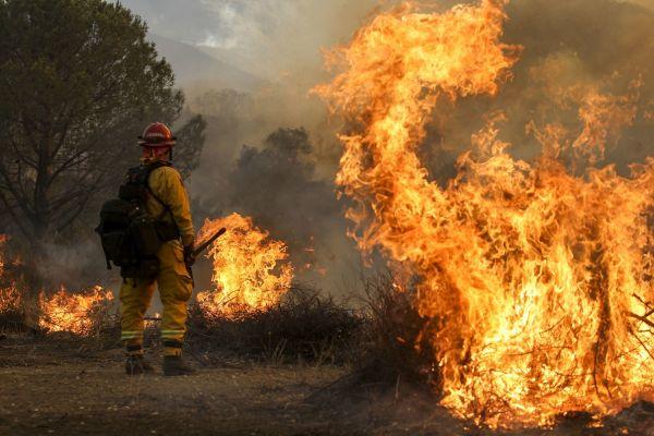 Un pompier priveste un incendiu in Santa Clarita, California. Mii de localnici au fost evacuati in urma extinderii a doua incendii de vegetatie, din cauza temperaturilor ridicate si a secetei. Foto: AP Photo/Ringo H.W. Chiu/Agerpres