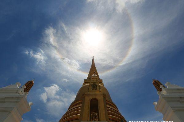 Un halou solar, surprins deasupra unei pagode din Bangkok, Thailanda. Haloul este un inel de lumina vizibil in jurul Soarelui sau al Lunii, format din cristale minuscule de gheata din norii Cirrus, aflati in stratul superior al atmosferei.