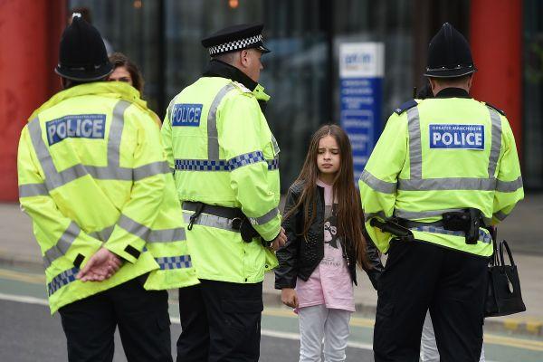 Politistii vorbesc cu localnicii din zona in care a avut loc atacul terorist din Manchester. 22 de persoane au murit si alte peste 59 sunt ranite, dupa ce un atacator sinucigas s-a aruncat in aer la un concert la Manchester Arena. Foto: AFP/Getty Images