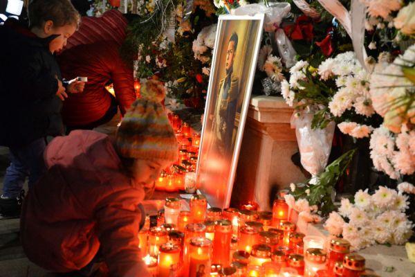 Câțiva copii aprind lumânări la Palatul Regal. Peste 16.000 de oameni au stat joi noapte la coadă ca să-şi ia rămas bun de la Regele Mihai I al României. Foto: Agerpres