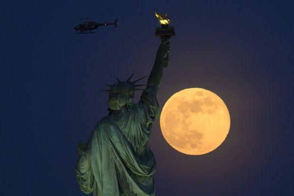 Un elicopter trece pe deasupra Statii Libertății, luminată de luna plină, în New York. Foto: JOHANNES EISELE/AFP/Getty Images/Guliver