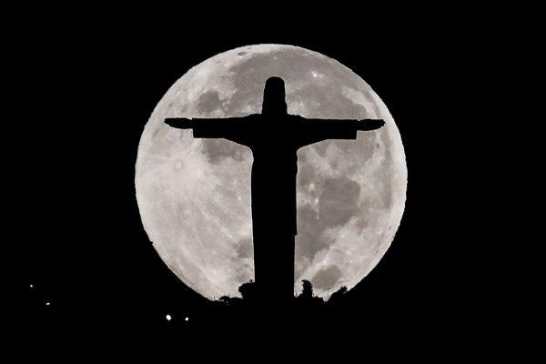 Monumentul Cristo Rey din Cali, Columbia, fotografiat cu luna plină în spate. Foto: LUIS ROBAYO/AFP/Getty Images/Guliver