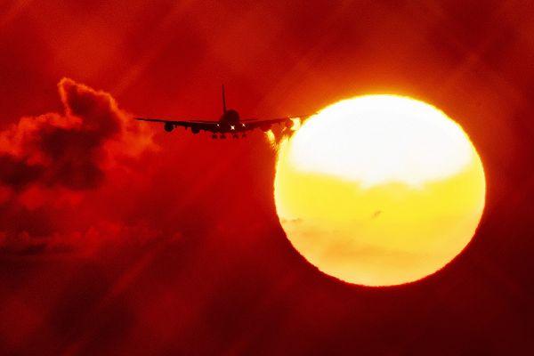 Un avion trece prin fața soarelui care răsare, pregătindu-se să aterizeze pe aeroportul din Frankfurt, Germania. Foto: Agerpores/AP Photo/Michael Probst